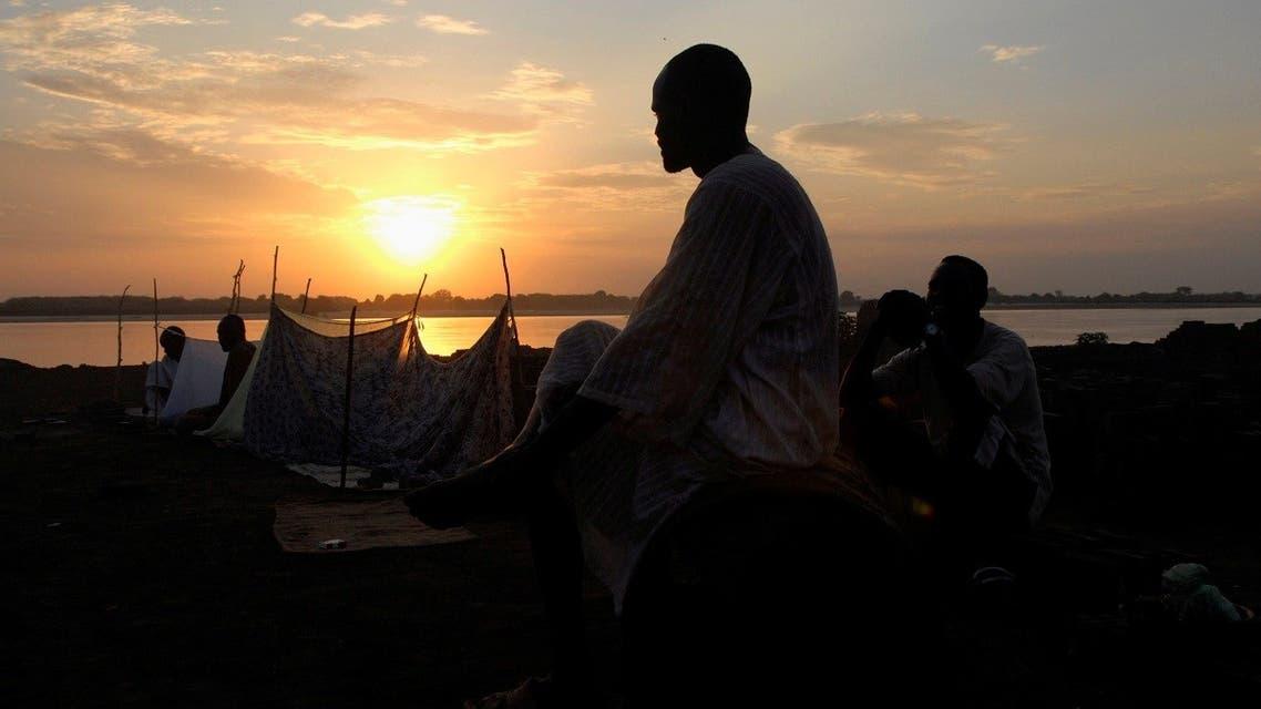 Sudanese men sit on the banks of the flood-swollen Blue Nile during sunset outside Sudan's capital Khartoum. (File photo: Reuters)