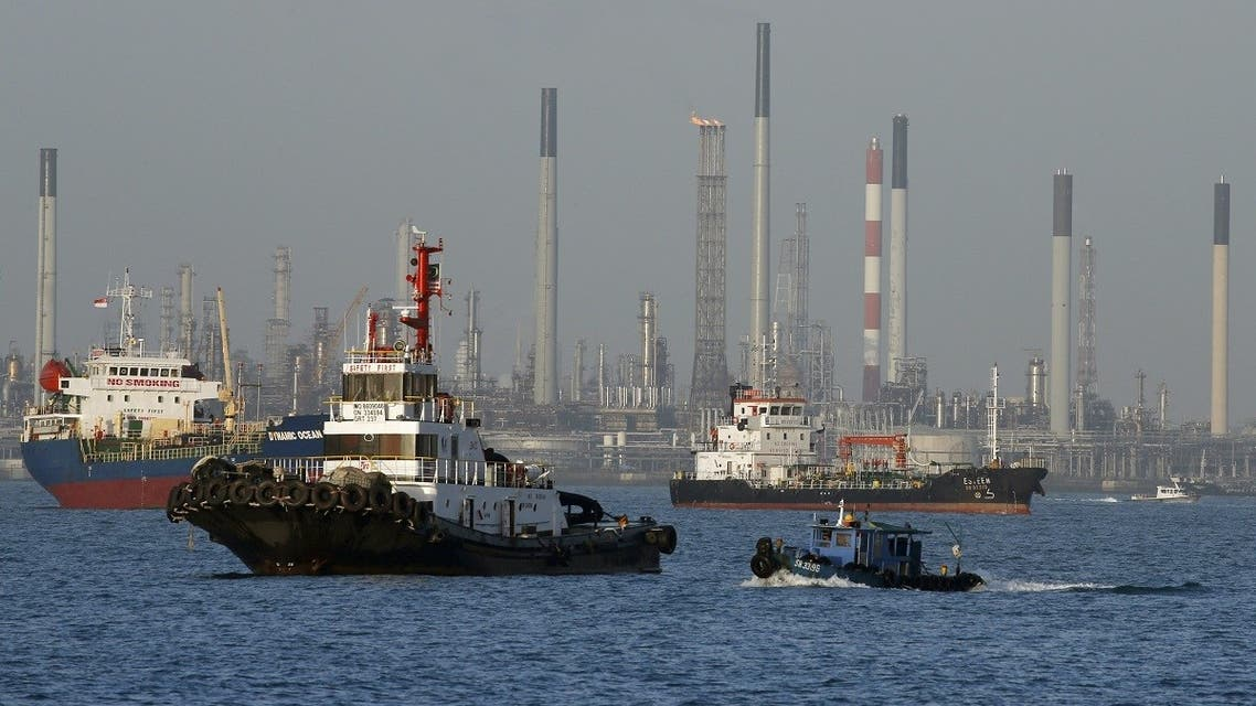 Vessels pass an oil refinery in the waters off the southern coast of Singapore. (Reuters)
