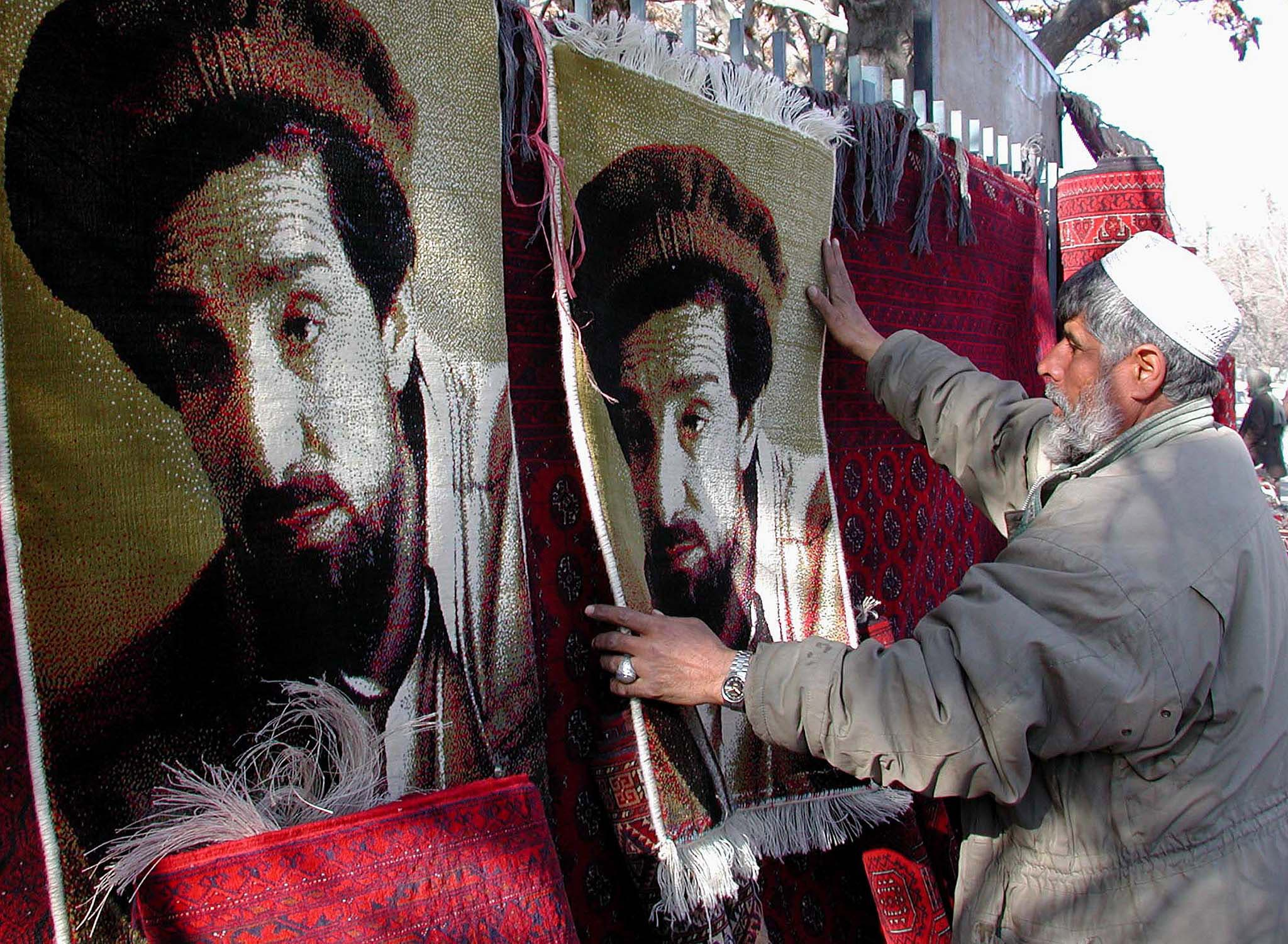 An Afghan man sells carpets with the picture of assassinated Northern Alliance leader Ahmad Shah Massoud on them in a Kabul market on January 24, 2002. (Reuters)