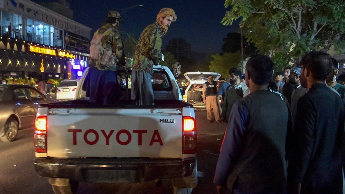 Taliban fighters stand on a pickup truck outside a hospital as volunteers bring injured people for treatment after two powerful explosions near the airport in Kabul, Aug. 26, 2021. (AFP)