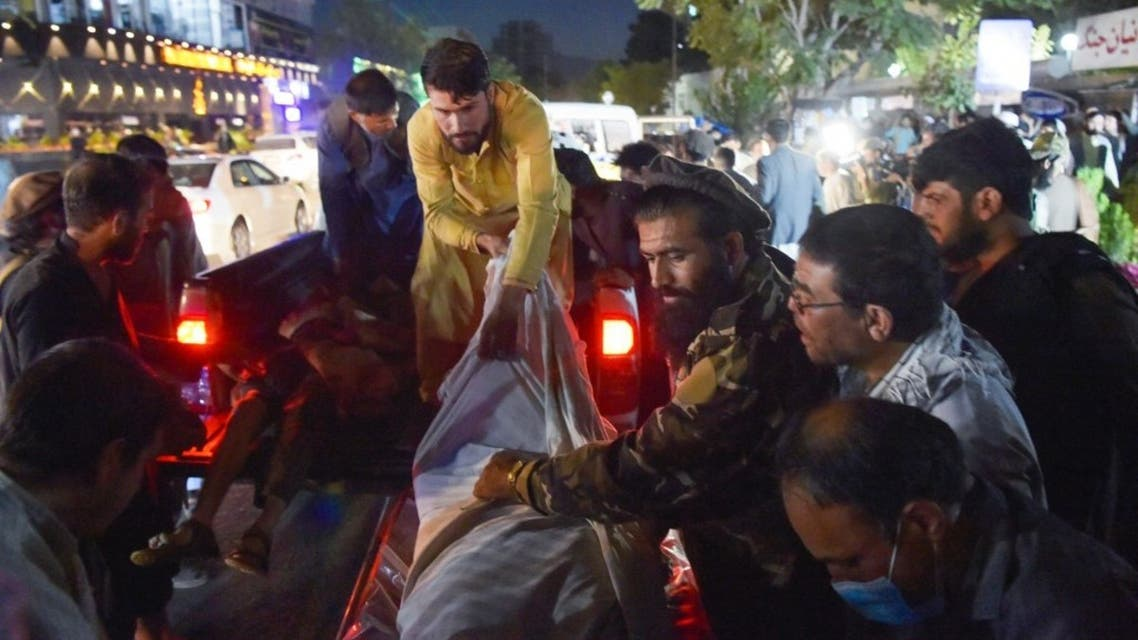 Volunteers and medical staff unload bodies from a pickup truck outside a hospital after two powerful explosions, which killed at least six people, outside the airport in Kabul on August 26, 2021. (AFP)