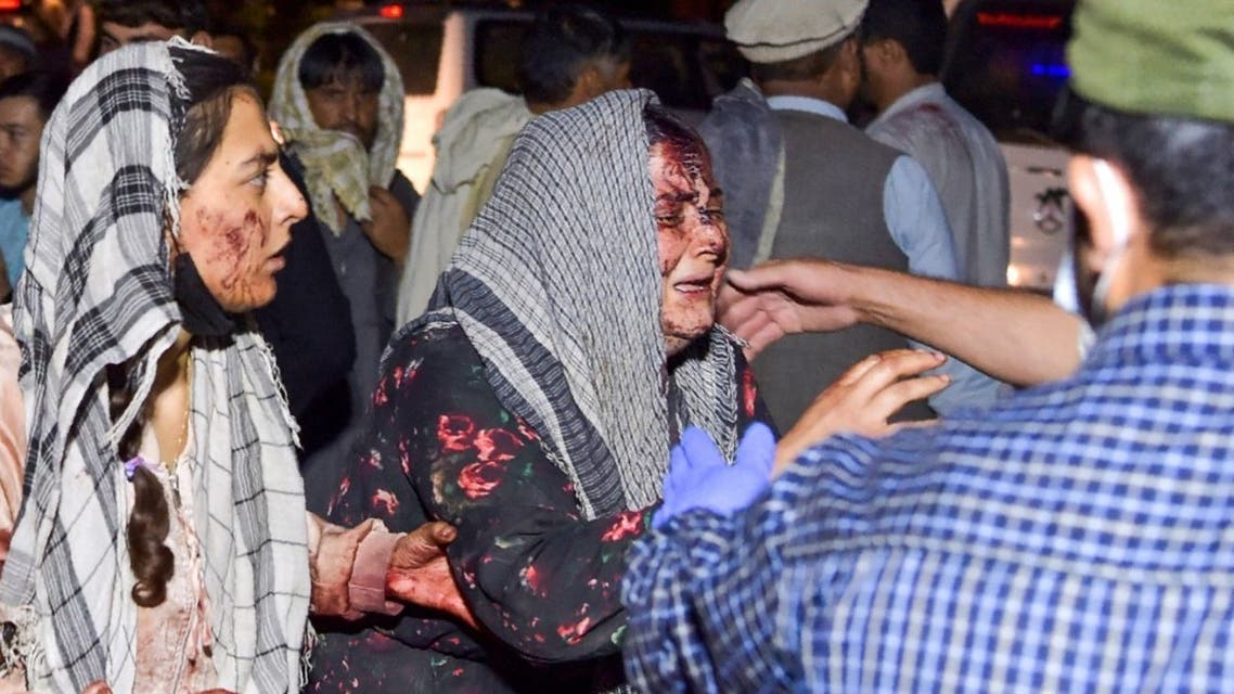 Wounded women arrive at a hospital for treatment after two blasts, which killed at least five and wounded a dozen, outside the airport in Kabul on August 26, 2021. (AFP)