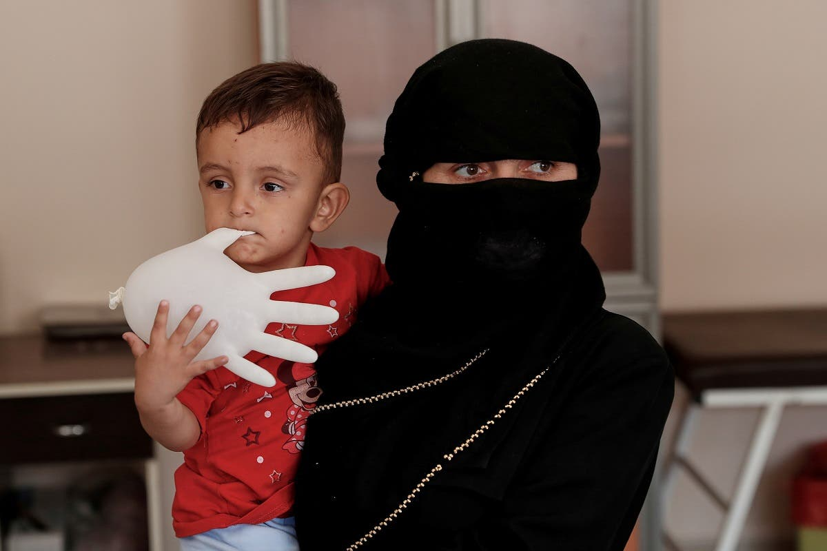 Afghan migrant Benevse and her two-year old son Rehimullah, caught by Turkish security forces after crossing illegally into Turkey from Iran, wait for a medical check at a migrant processing centre in the border city of Van, Turkey, on August 22, 2021. (Reuters)