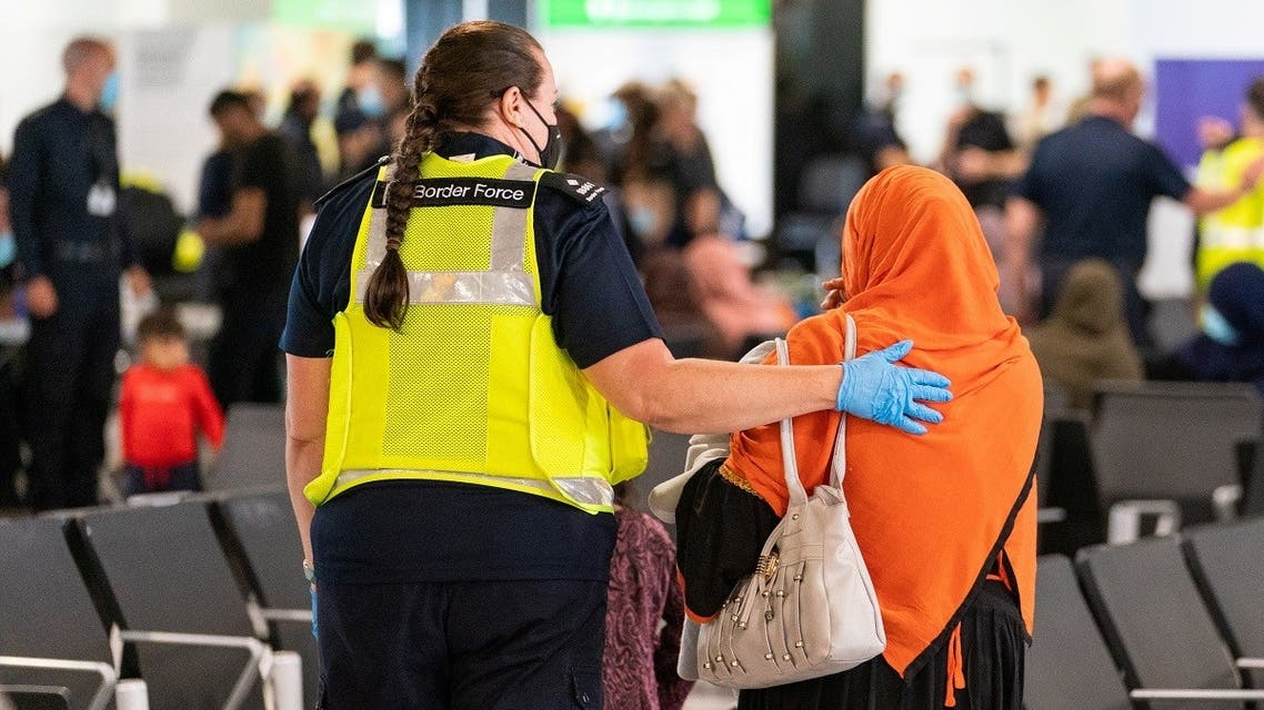 A member of Border Force staff assists a female evacuee as refugees arrive from Afghanistan at Heathrow Airport, in London, Britain, on August 26, 2021. (Reuters)