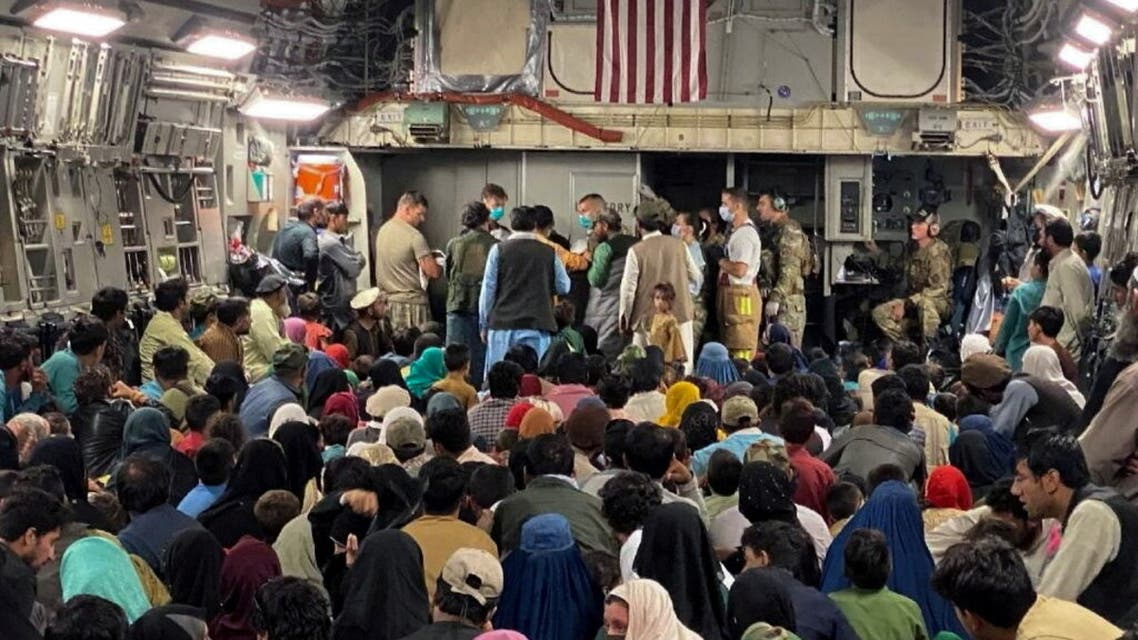 A newborn baby is looked after prior taking off with other Afghan evacuees on a C-17 Globemaster III at a Middle East staging area August 23, 2021. (Reuters)