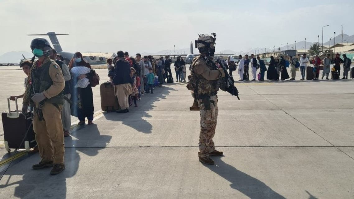 This handout picture released and taken by the Italian Defence press office on August 22, 2021 shows soldiers on the tarmac past passengers, who fled Afghanistan, waiting to board on an Italian military aircraft at Kabul airport, to fly to Rome Fiumici. (AFP)