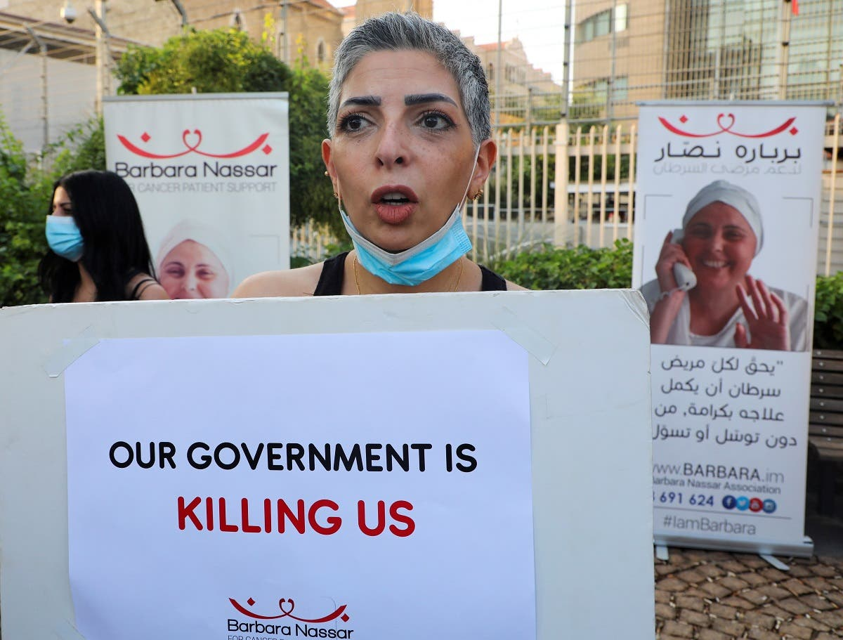 A cancer patient holds a sign, during a sit-in demonstration as shortages of cancer medications spread, in front of the UN headquarters in Beirut, Lebanon August 26, 2021. (Reuters)