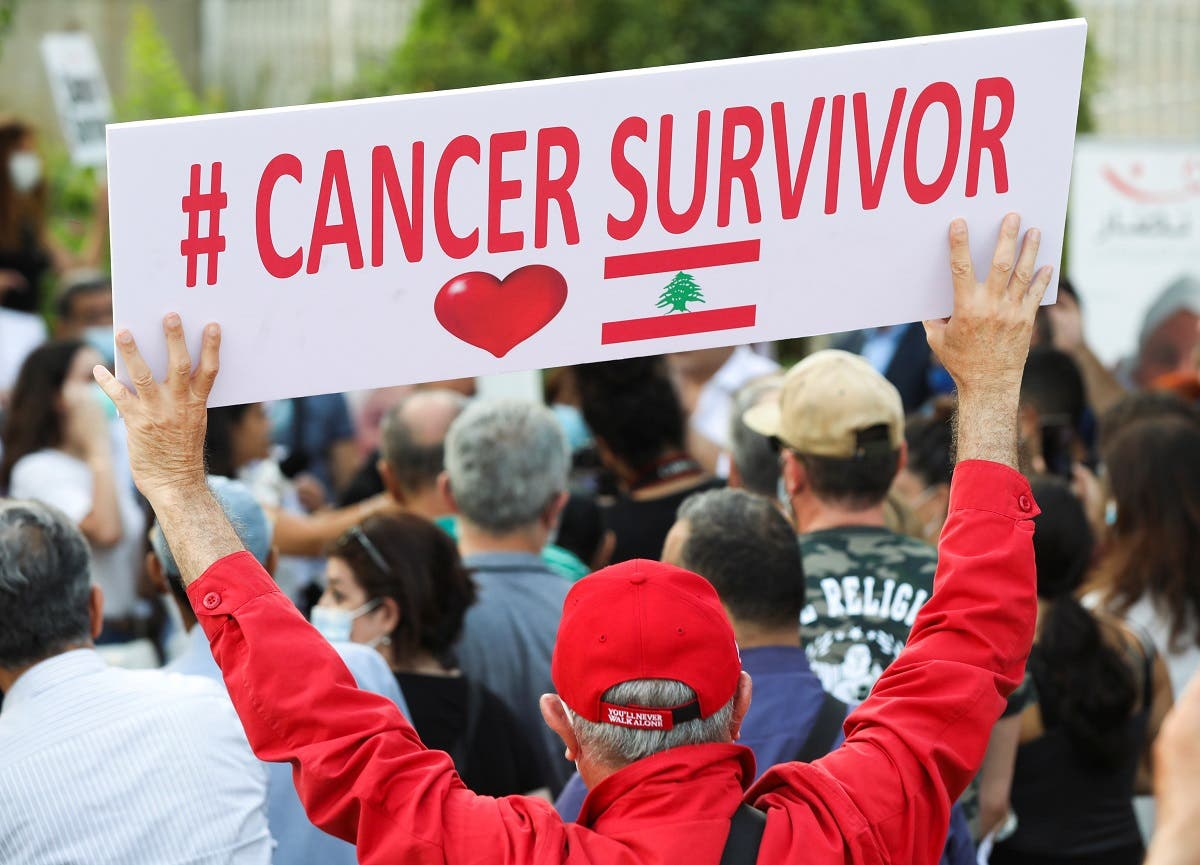 A man holds a sign during a sit-in demonstration as shortages of cancer medications spread, in front of the UN headquarters in Beirut, Lebanon, on August 26, 2021. (Reuters)