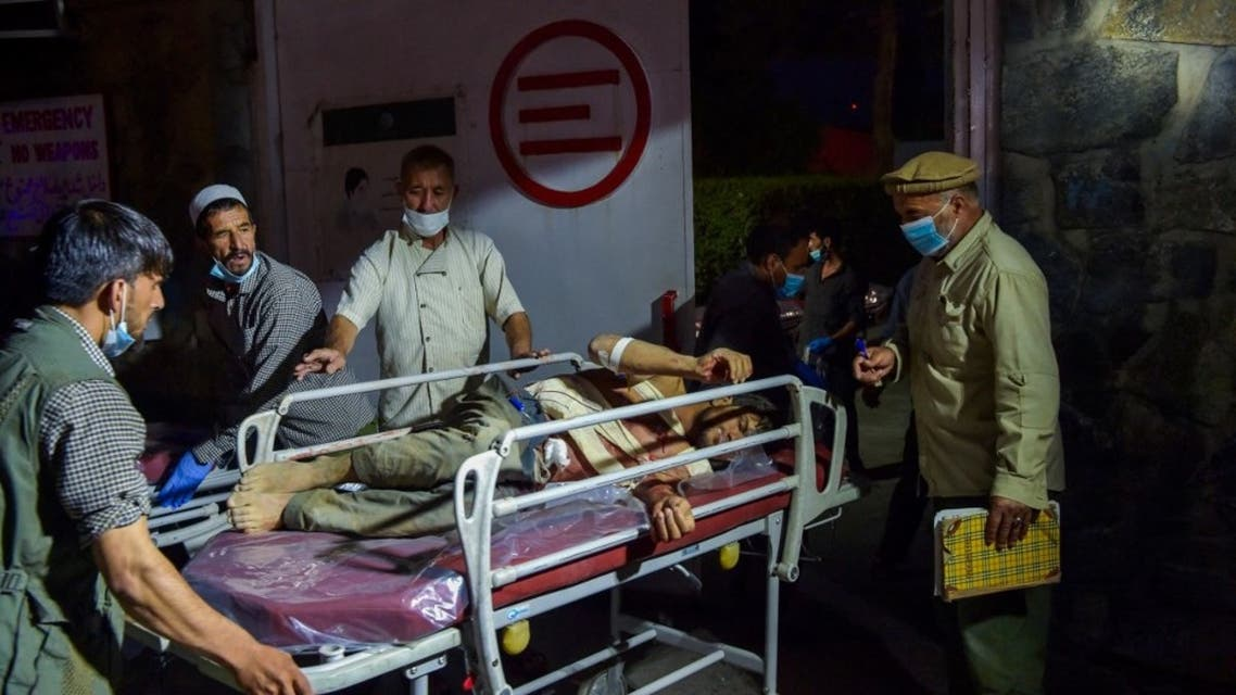 Medical and hospital staff bring an injured man on a stretcher for treatment after two powerful explosions, which killed at least six people, outside the airport in Kabul on August 26, 2021. (AFP)