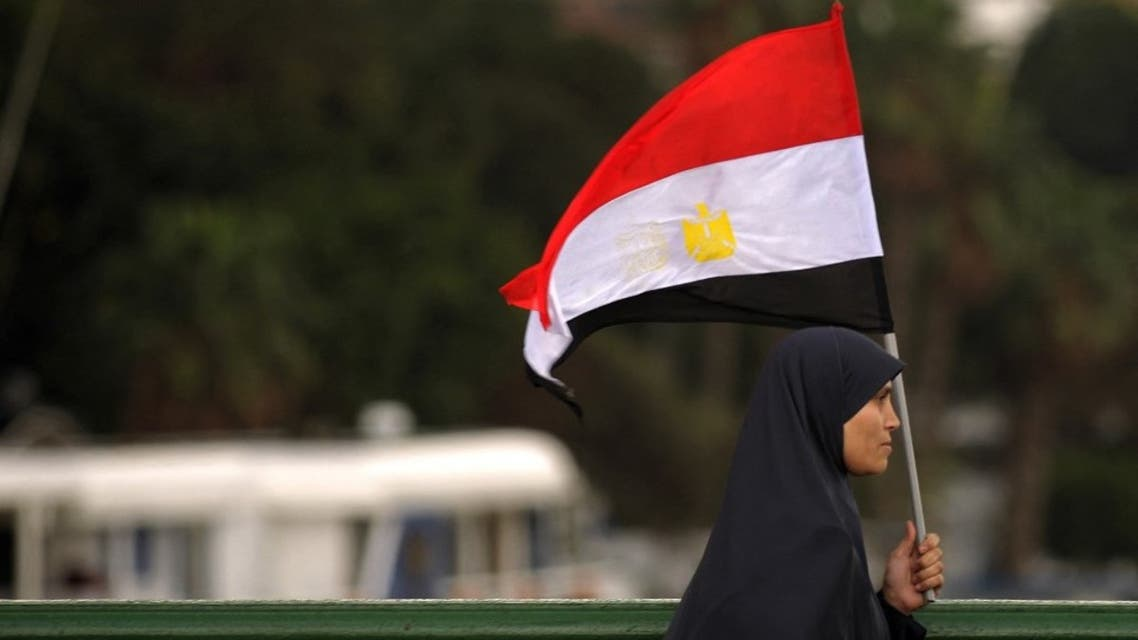 An Egyptian woman walks with her national flag on Qasr el-Nil bridge leading to Cairo's Tahrir Square. (File photo: AFP)