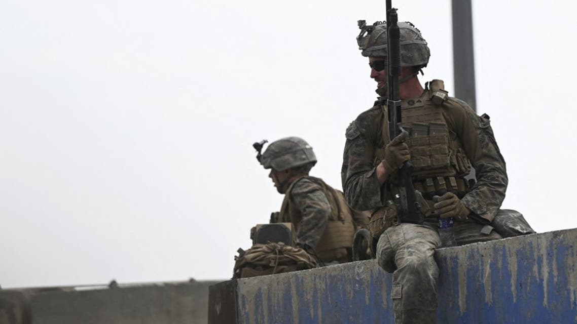 US soldiers sit on a wall as Afghans gather on a roadside near the military part of the airport in Kabul on August 20, 2021. (AFP)