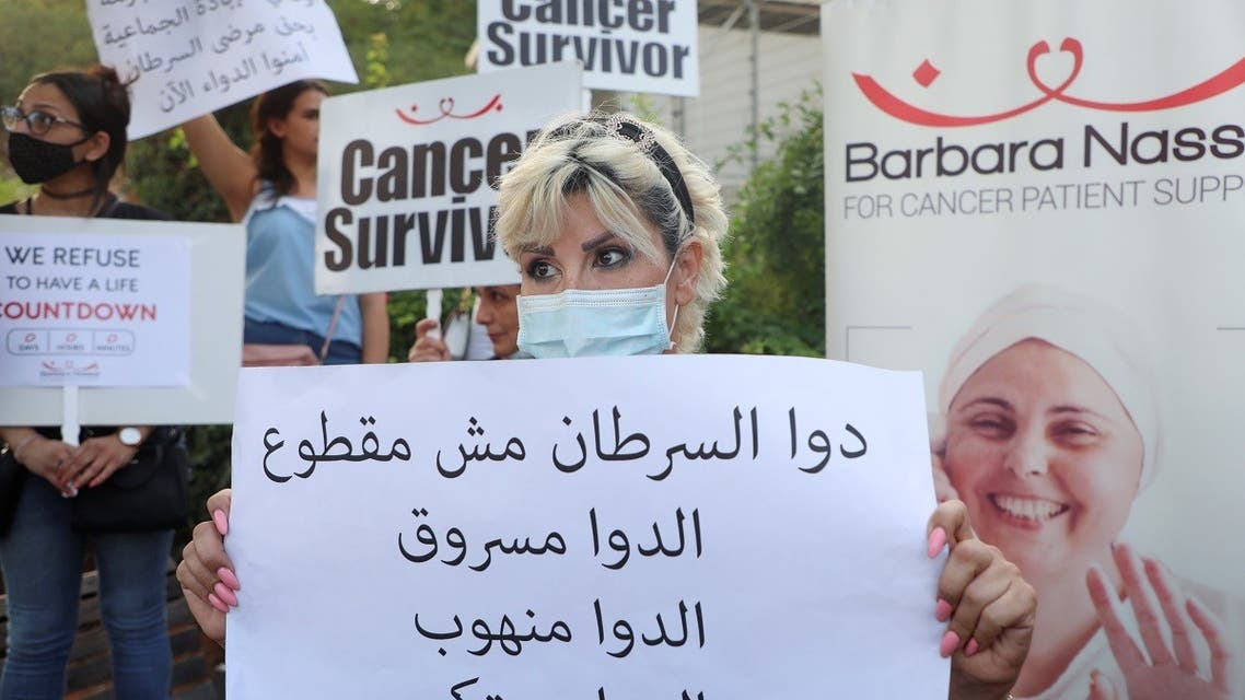 Christine Tohme, a cancer patient, holds a sign during a sit-in demonstration as shortages of cancer medications spread, in front of the UN headquarters in Beirut, Lebanon August 26, 2021. (Reuters)