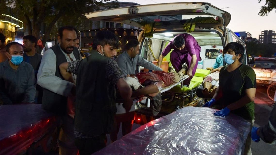 Volunteers and medical staff bring an injured man for treatment after two powerful explosions, which killed at least six people, outside the airport in Kabul on August 26, 2021. (AFP)