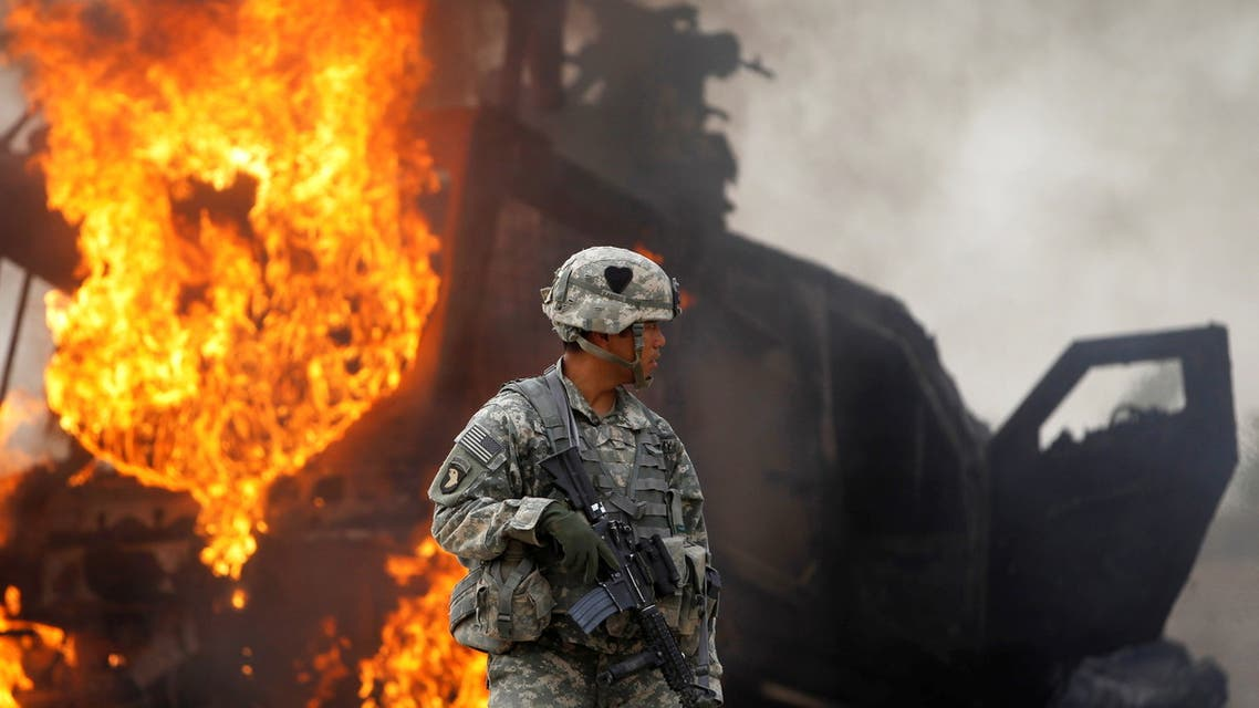 Captain Melvin Cabebe with the US Army's 1-320 Field Artillery Regiment, 101st Airborne Division stands near a burning M-ATV armored vehicle after it struck an improvised explosive device (IED) near Combat Outpost Nolen in the Arghandab Valley north of Kandahar, Afghanistan. (File photo: Reuters)