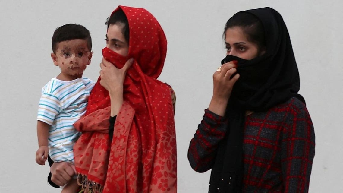 This picture taken during a media visit organised by the Qatari authorities on August 21, 2021, shows Afghan women and a child inside a villa complex near the centre of the Qatari capital Doha. (AFP)