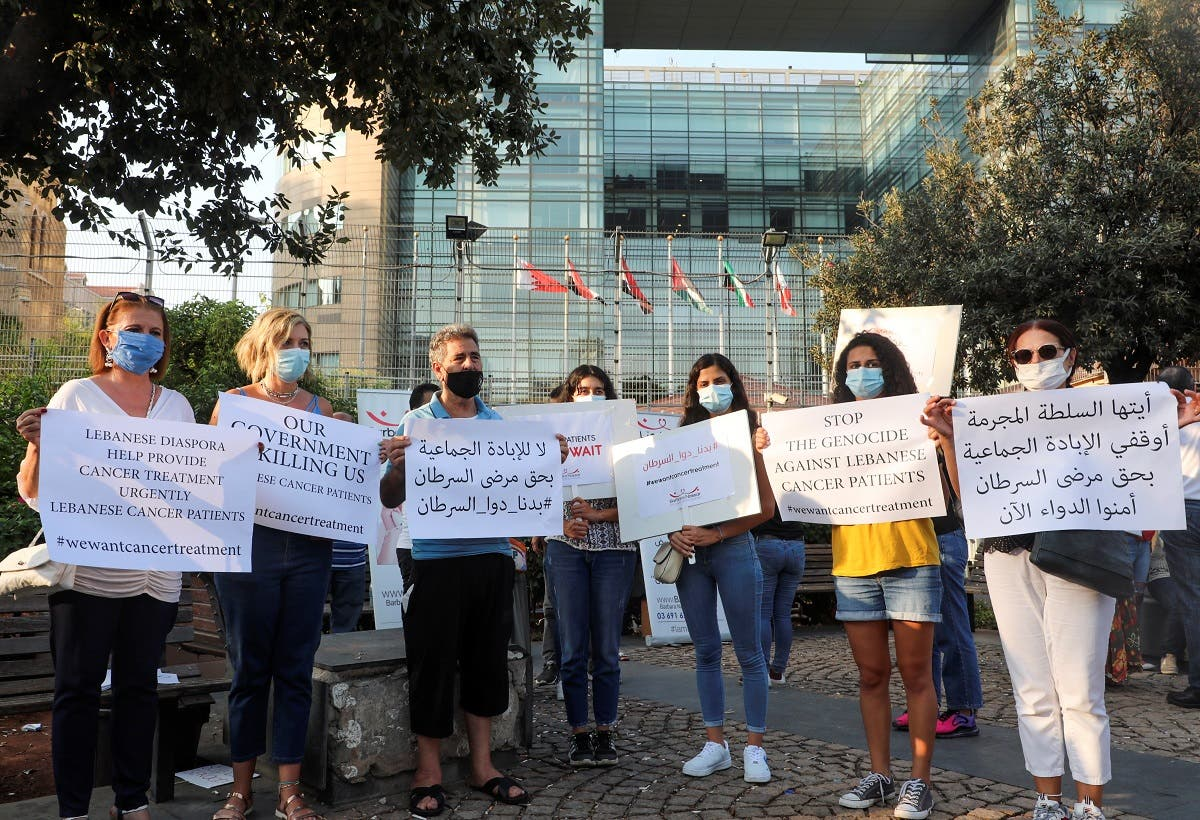 A file photo shows people hold signs during a sit-in demonstration as shortages of cancer medications spread, in front of the UN headquarters in Beirut, Lebanon August 26, 2021. (Reuters)