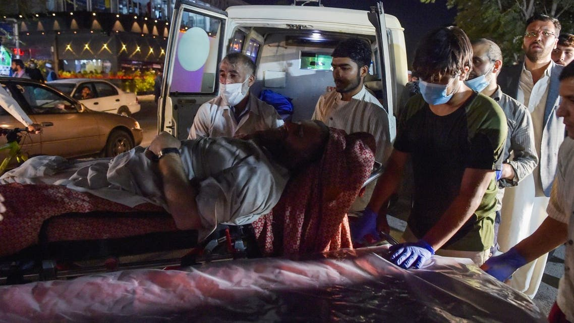 Volunteers and medical staff bring an injured man on a stretcher to a hospital for treatment after two powerful explosions, which killed at least six people, outside the airport in Kabul on August 26, 2021.