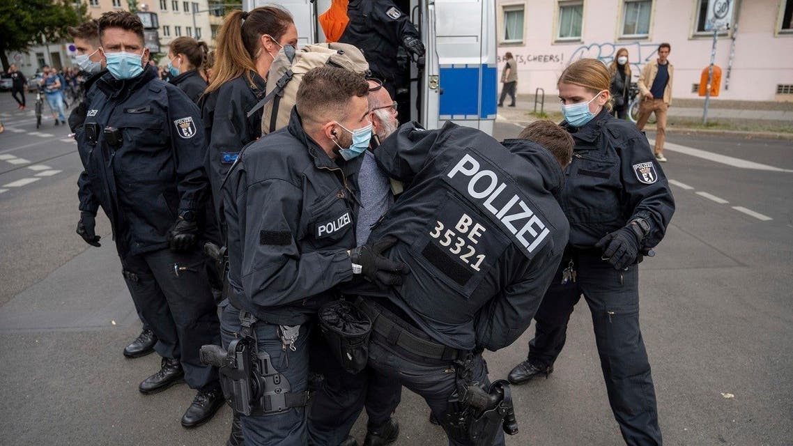 Police restrain a demonstrator, during a protest against coronavirus restrictions, in Berlin, Saturday, Aug. 28, 2021. (AP)