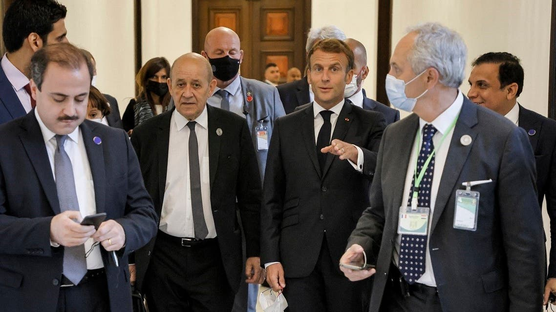 French President Emmanuel Macron (C R) and Foreign Minister Jean-Yves Le Drian (C L) leave the regional summit conference in the Iraqi capital Baghdad on August 28, 2021. (Ludovic Marin/AFP)