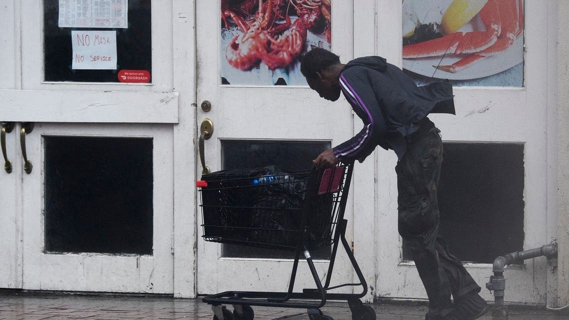 A person pushes a shopping cart through rain and high winds past a closed restaurant on Canal Street in New Orleans, Louisiana on August 29, 2021 during Hurricane Ida. (AFP)