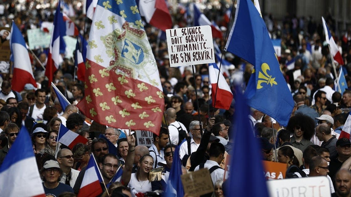 """Protesters holding French flags and the fleur-de-lys royalist symbol take part in a rally called by the French nationalist party """"Les Patriotes"""" (The Patriots) against the compulsory COVID-19 vaccination for certain workers and the mandatory use of the health pass, in Paris on August 28, 2021.  Sameer Al-Doumy/AFP)"""