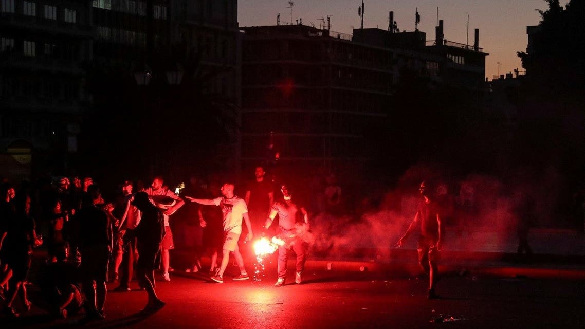 A man holds a flare during a protest against coronavirus disease (COVID-19) vaccinations outside the parliament building, in Athens, Greece, August 29, 2021. (Reuters)
