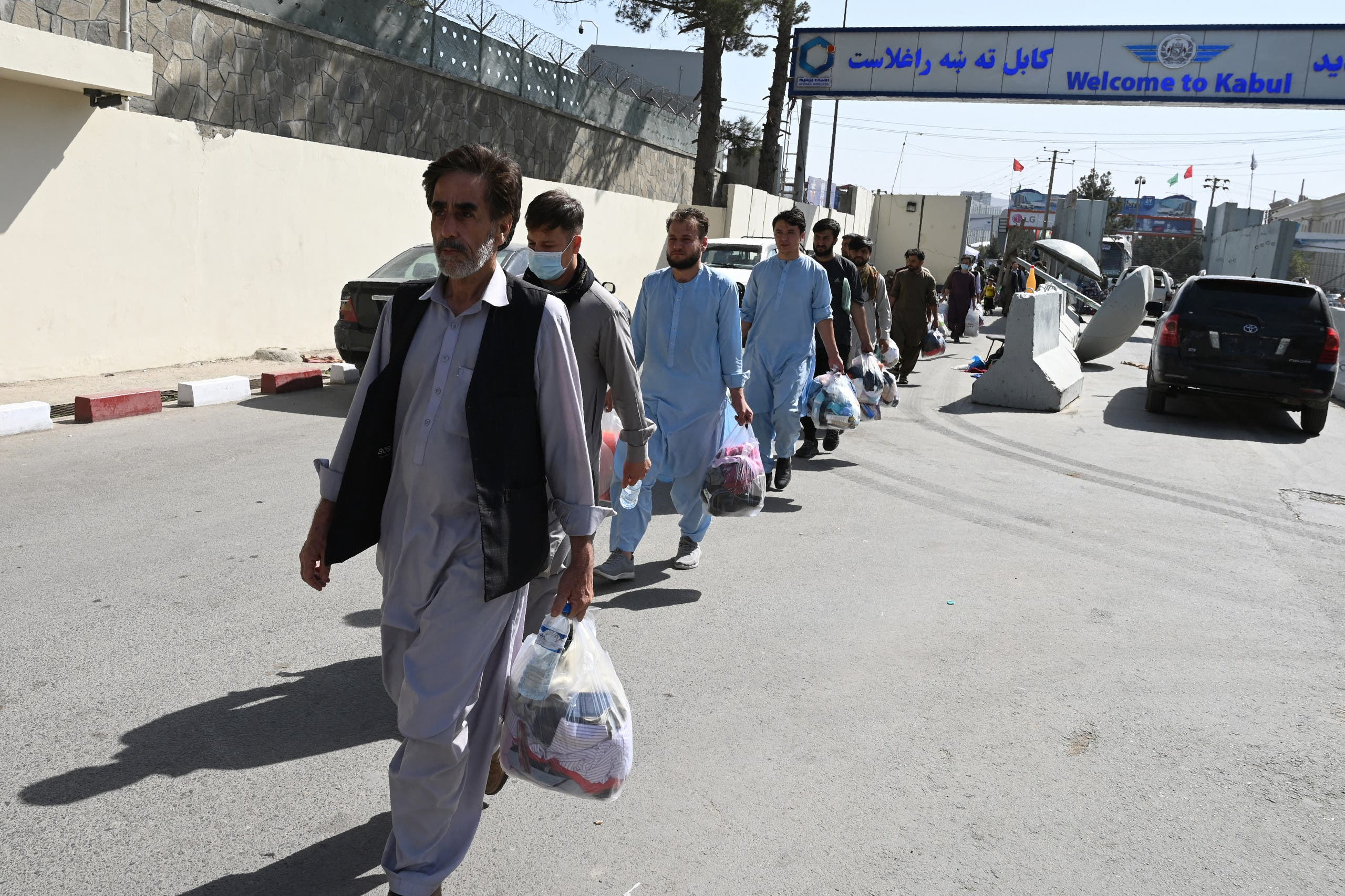 Afghans hoping to leave Afghanistan walk to the main entrance gate of Kabul airport in Kabul on August 28, 2021, following the Taliban stunning military takeover of Afghanistan. (AFP)