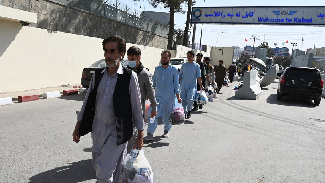 Afghans hoping to leave Afghanistan walk to the main entrance gate of Kabul airport in Kabul on August 28, 2021, following the Taliban military takeover of Afghanistan. (AFP)