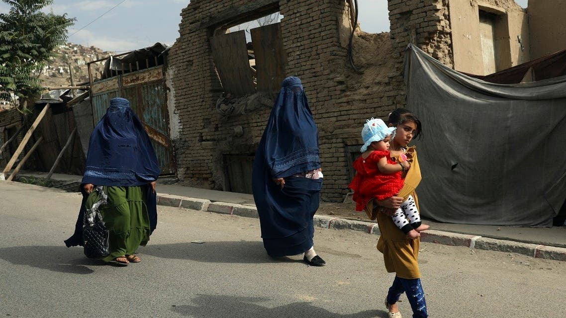 Afghan women in burqas and children walk on a street in Kabul, Afghanistan, Sunday, Aug. 22, 2021. (AP)