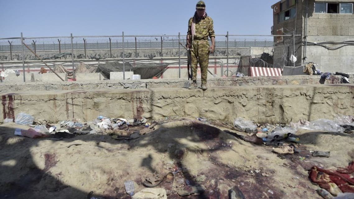 A Taliban fighter stands guard at the site of the August 26 twin suicide bombs, which killed scores of people including 13 US troops, at Kabul airport on August 27, 2021. (AFP)