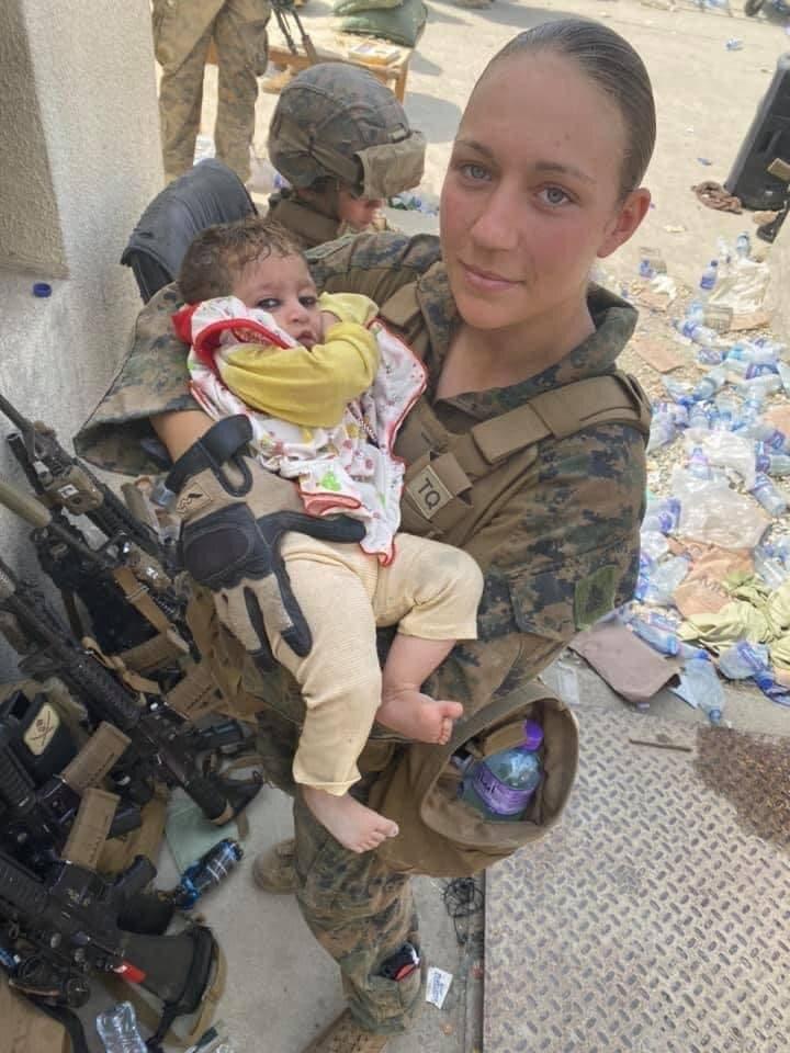 نيكول جي تحمل طفلاً أفغانياً في مطار كابل