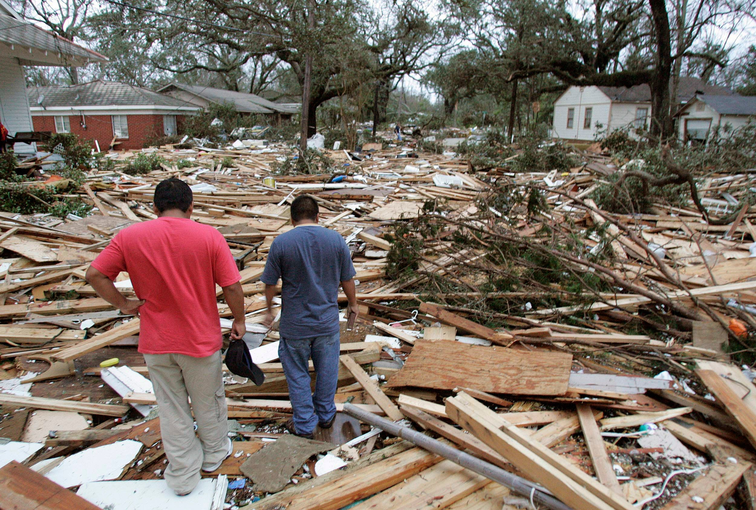 People walk amidst the remains of the St Charles Condominiums and Sadler Apartments in Biloxi, Mississippi, August 29, 2005, which were pushed up between the private homes on St Charles Street by the storm surge from Hurricane Katrina. (Reuters)