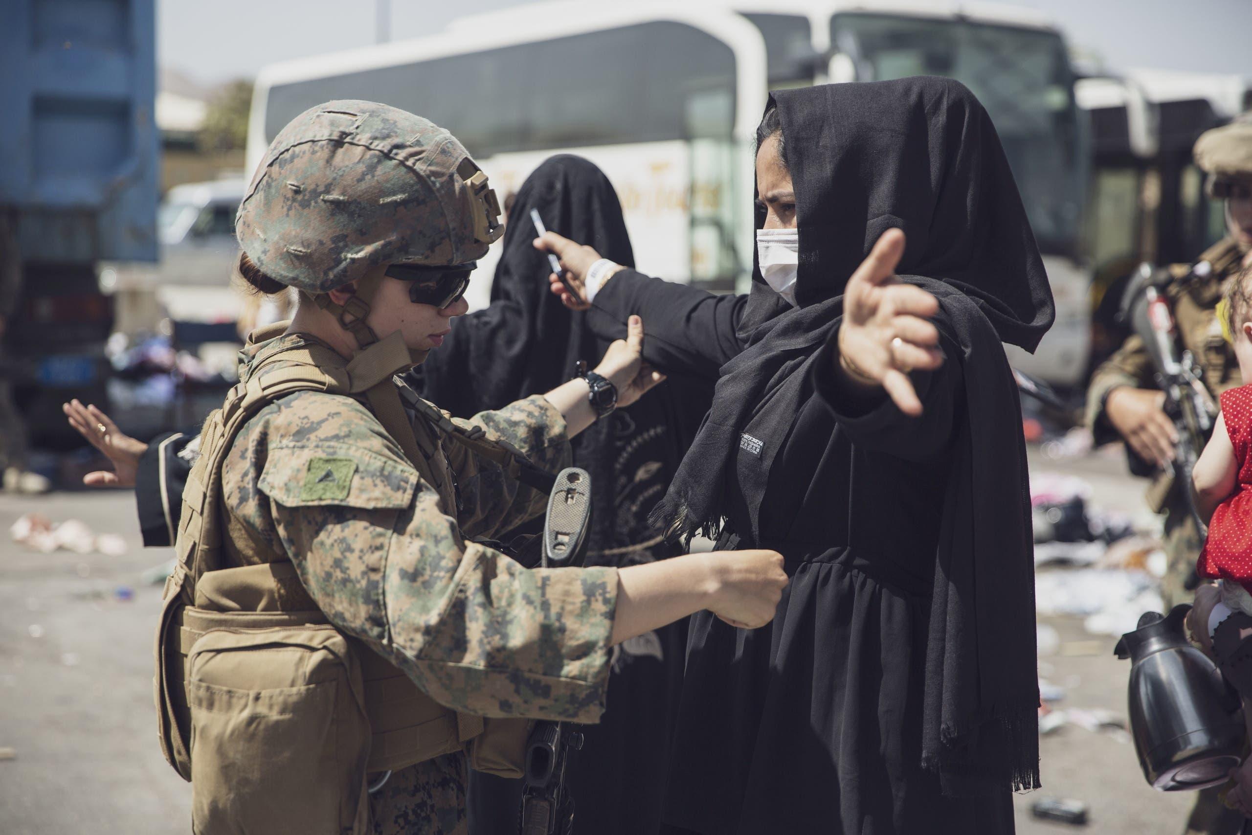 جندية أميركية تفتش سيدة أفغانية في مطار كابل السبت
