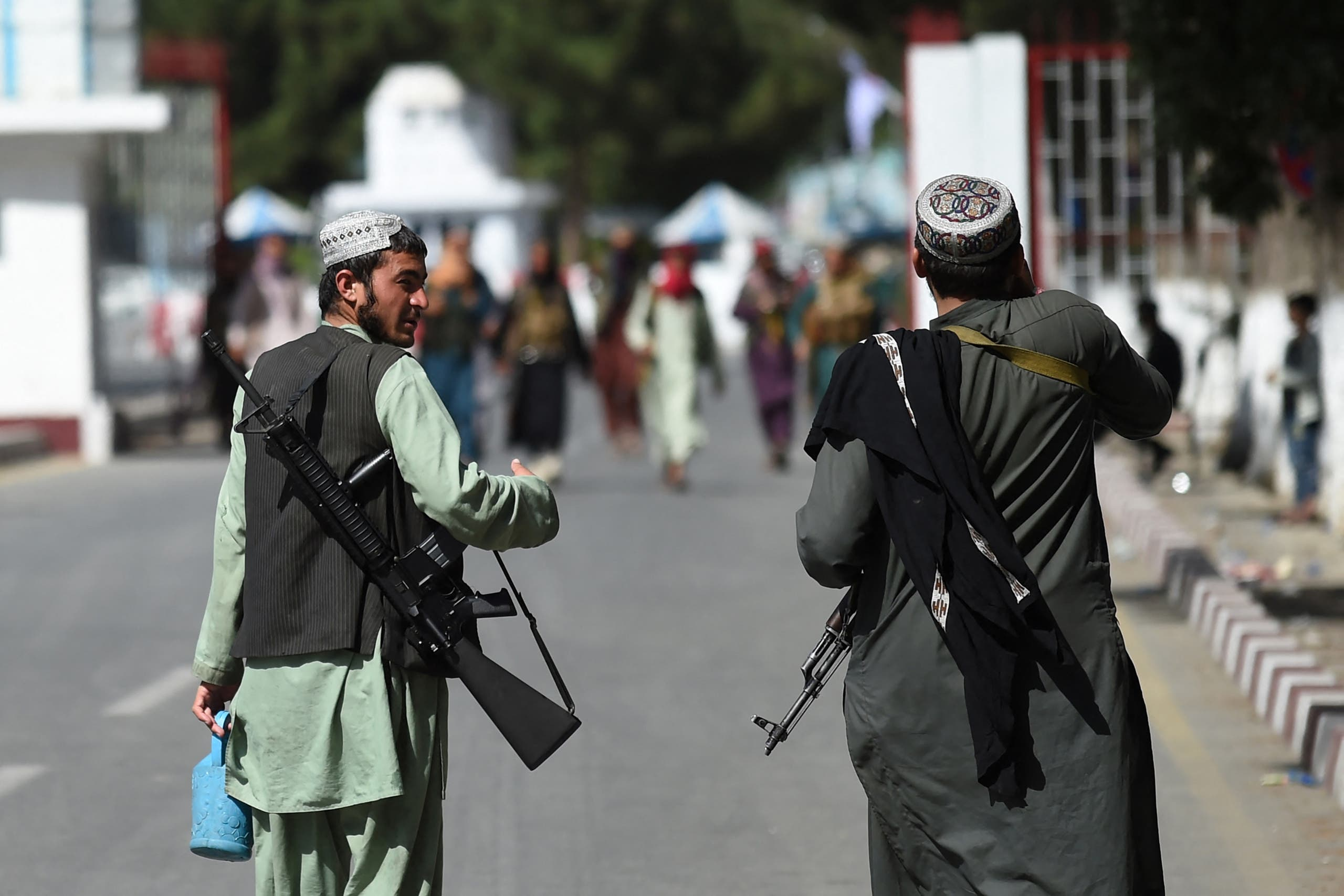 Taliban fighters walk at the main entrance gate of Kabul airport in Kabul on August 28, 2021, following the Taliban stunning military takeover of Afghanistan. (AFP)