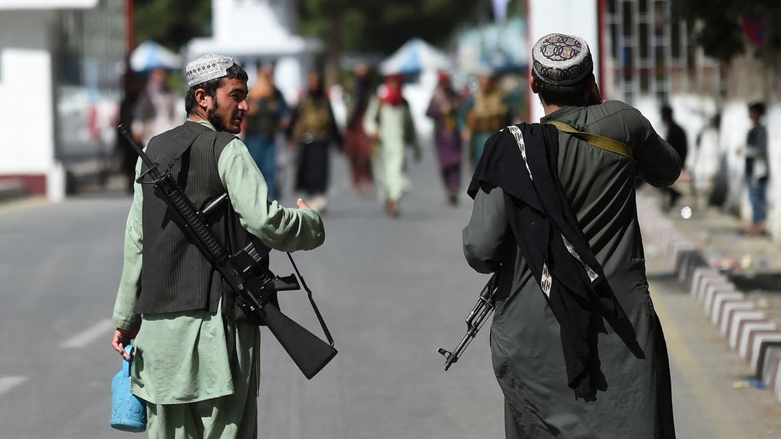 Taliban fighters walk at the main entrance gate of Kabul airport in Kabul on August 28, 2021, following the Taliban stunning military takeover of Afghanistan.
