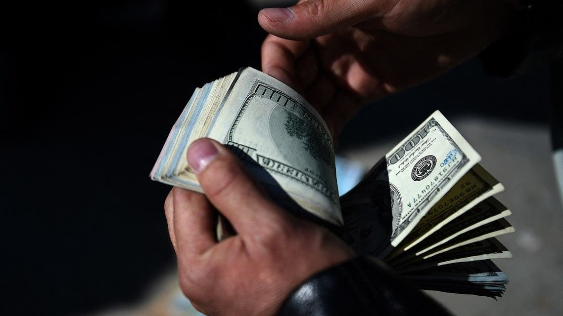 An Afghan money changer counts US dollars at the currency exchange Sarayee Shahzada market in Kabul on December 17, 2015. (Wakil Kohsar/AFP)