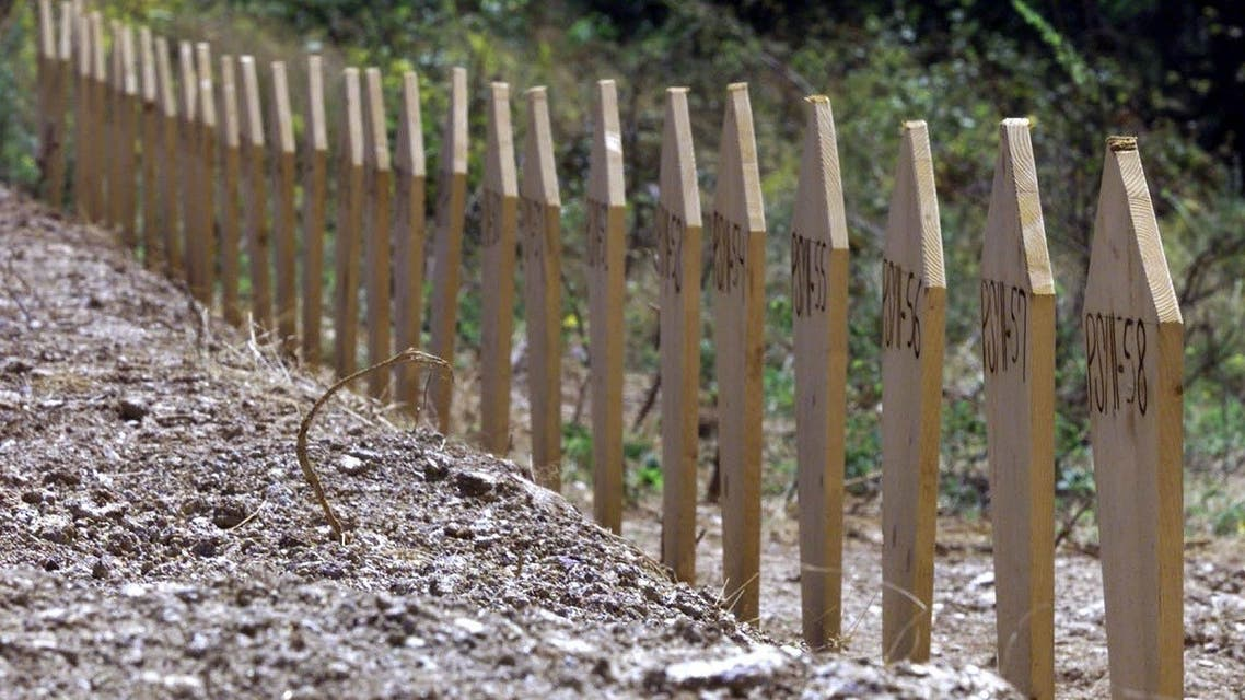 Dozens of graves marked with wooden markers where bodies of ethnic Albanians from Kosovo were buried are seen in this July 18, 2001 file photo, after they were unearthed from a mass grave in Petrovo Selo, about 150 kilometers east of Belgrade. (AP/Darko Vojinovic)