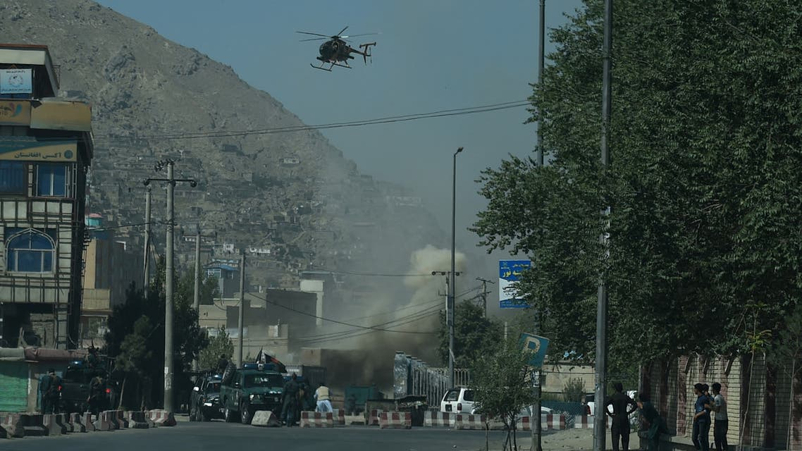 Smoke and dust (C) rise following an air strike from an Afghan military helicopter during ongoing clashes between Afghan security forces and militants near the Eid Gah Mosque in Kabul on August 21, 2018. Military helicopters were firing above a mosque in Kabul's old quarter Tuesday as officials said fighting had broken out between security forces and militants in the Afghan capital, with a barrage of rockets striking the city.  WAKIL KOHSAR / AFP