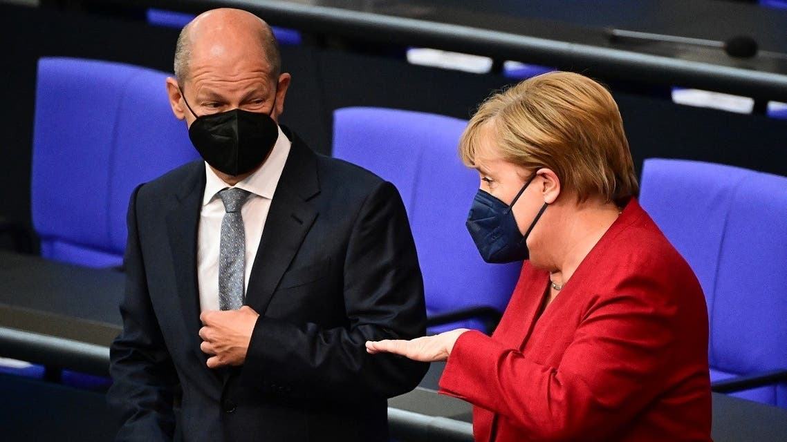 German Finance Minister, Vice-Chancellor and the Social Democrats (SPD) candidate for Chancellor Olaf Scholz (L) and German Chancellor Angela Merkel talk ahead a plenary session at the German lower house of parliament Bundestag in Berlin on August 25, 2021. (Tobias Schwarz/AFP)