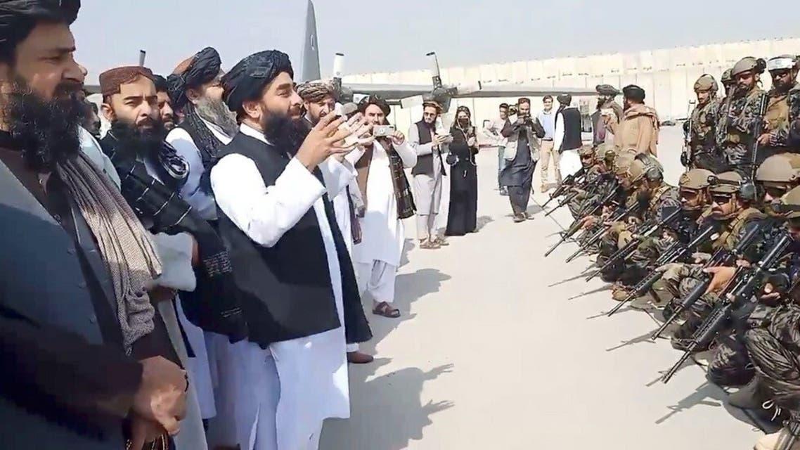 ذبيح الله مجاهد المتحدث باسم حركة طالبان يتحدث أمام مقاتلين من الحركة في مطار كابل