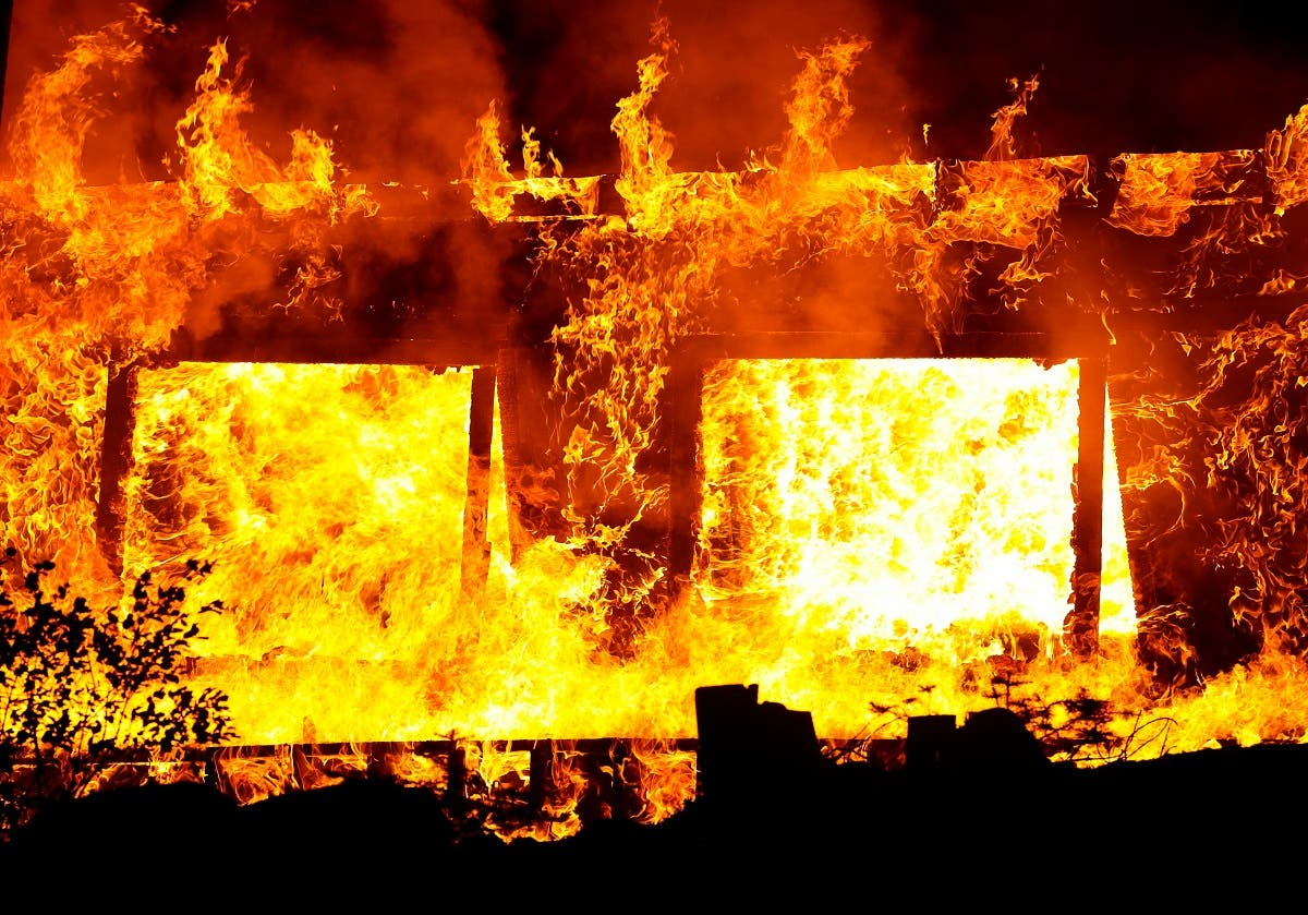 Flames are seen in the widows of a cabin burning in the Caldor Fire near Phillips, California, US. (Reuters)