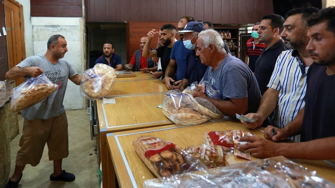People queue to buy bread from a bakery, after the central bank decided to effectively end subsidies on fuel imports, in Sidon, Lebanon, on August 13, 2021. (Reuters)