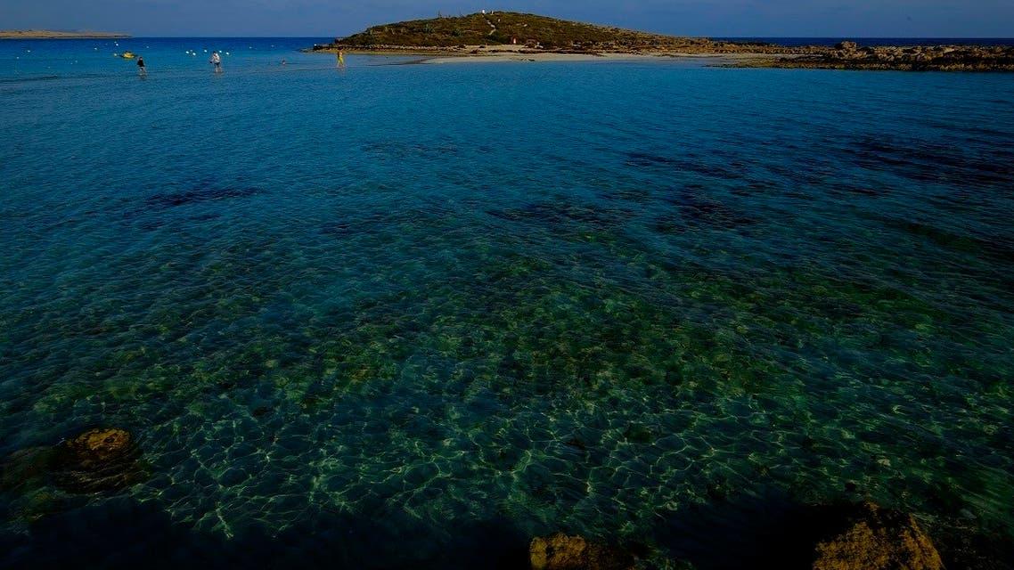 "People walk in the sea at ""Nissi Beach"" in southeast resort of Ayia Napa in the eastern Mediterranean island of Cyprus, Wednesday, April 28, 2021. (AP/Petros Karadjias)"