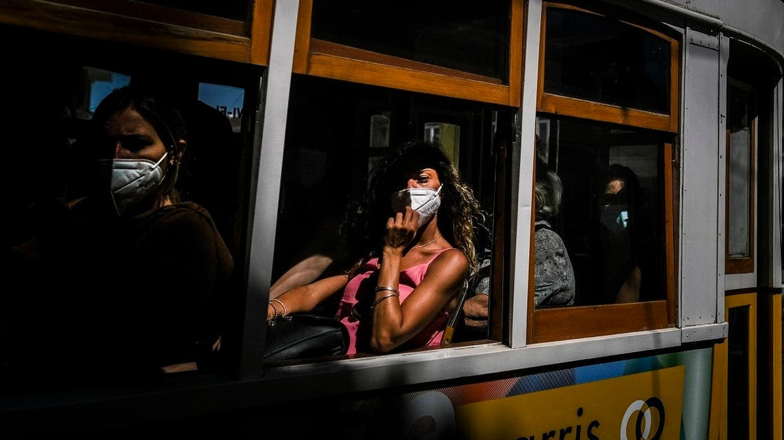 Tourists wearing face masks ride a tram in Lisbon on July 14, 2021. (Patricia De Melo Moreira/AFP)