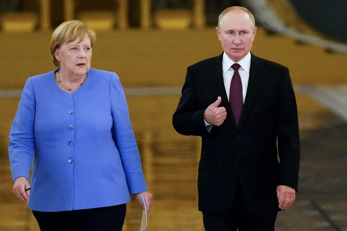 Russian President Vladimir Putin and German Chancellor Angela Merkel enter a hall during a news conference following their talks at the Kremlin in Moscow, Russia, on August 20, 2021. (Reuters)