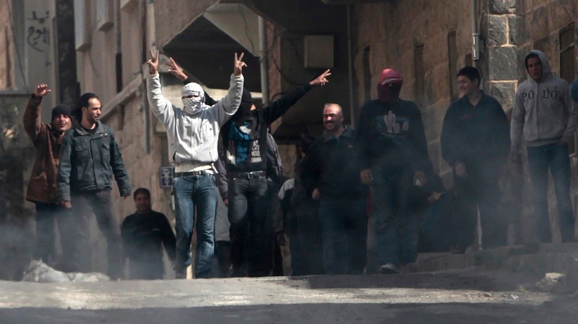 File photo of anti-Syrian government protesters flashing Victory signs as they protest in the southern city of Daraa, Syria. (AP)
