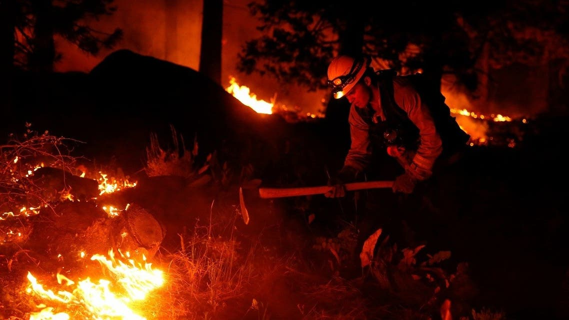 A fire fighter works a hand line behind houses along Santa Clause Drive as flames from the Caldor Fire burn near South Lake Tahoe, California, Aug. 30, 2021. (Reuters)