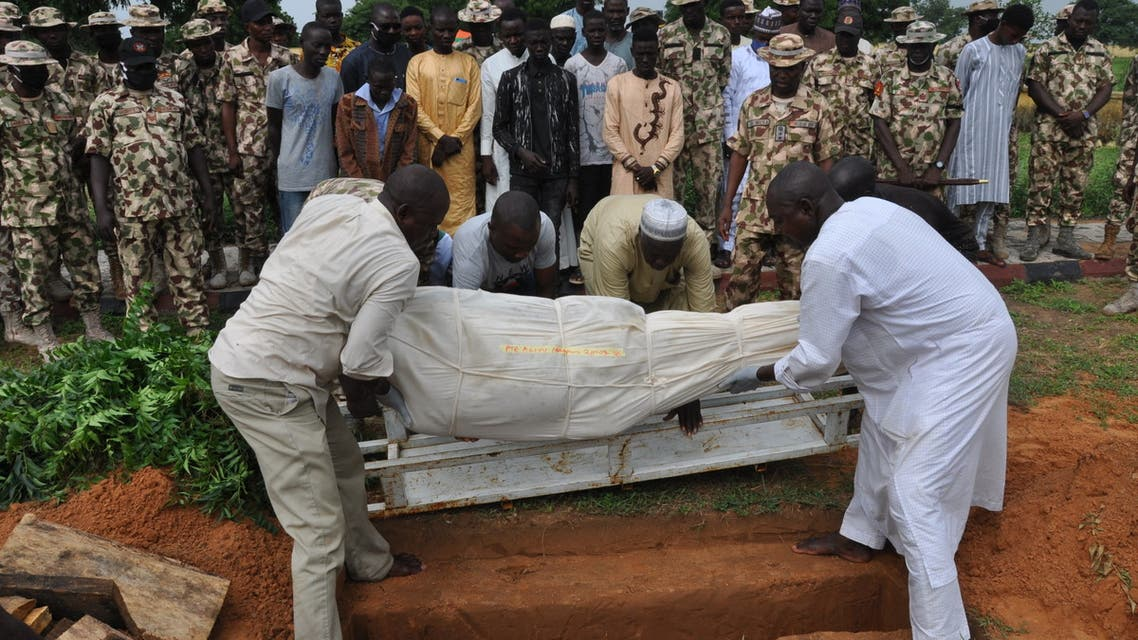 Nigerian soldiers and relatives look on as the body of a victim of the attack on vehicles carrying Borno governor Babagana Umara Zulum near the town of Baga on the shores of Lake Chad is buried during a the funeral in Maiduguri on September 26, 2020. The insurgents opened fire with machine guns and rocket-propelled grenades as the convoy was passing through a village close to the headquarters of the Multinational Joint Task Force (MNJTF), a military coalition of troops from Nigeria, Niger, Chad and Cameroon.