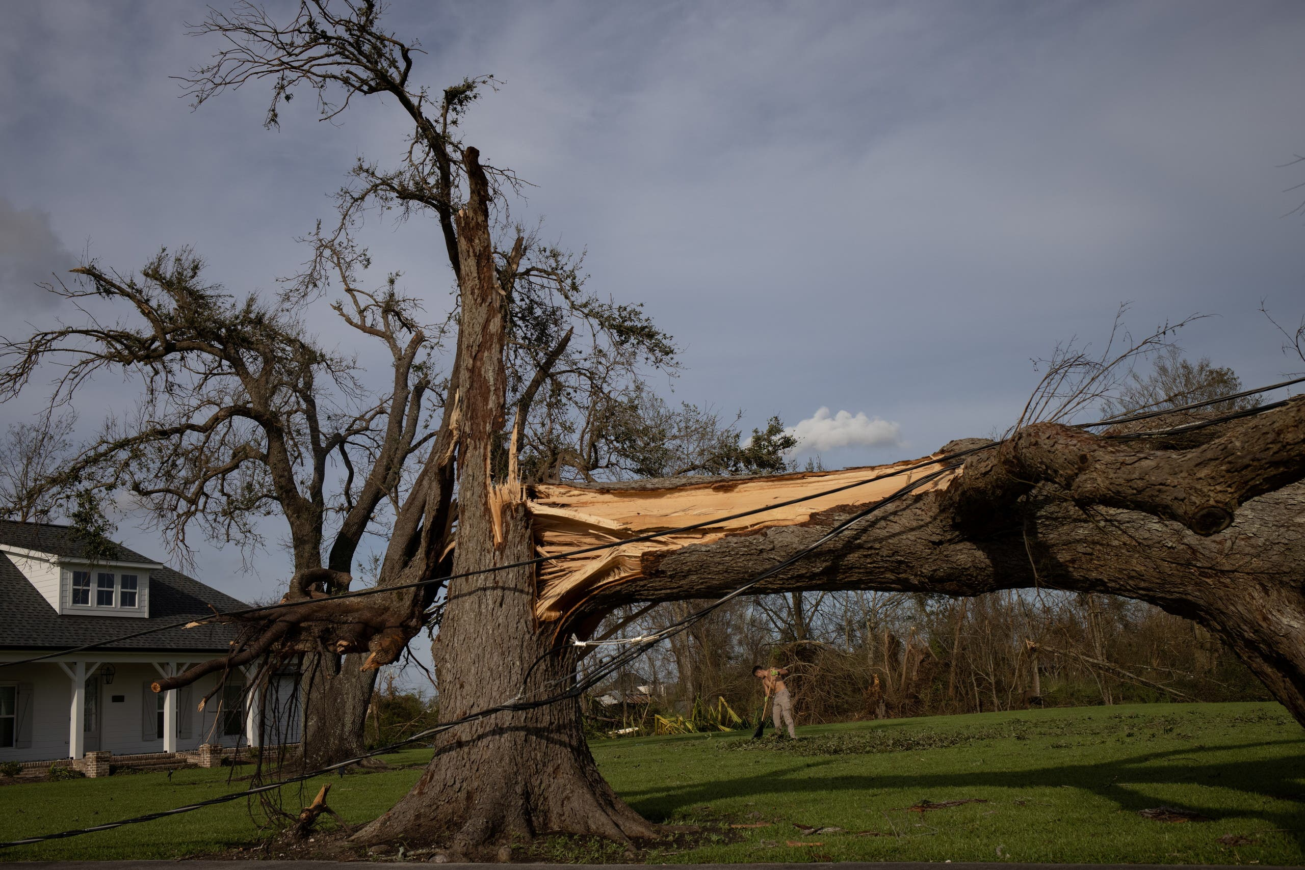 Local resident Kurt Charpentier rakes leaves past a fallen tree in his yard in the aftermath of Hurricane Ida in Bourg, Louisiana, US, August 30, 2021. (Reuters)