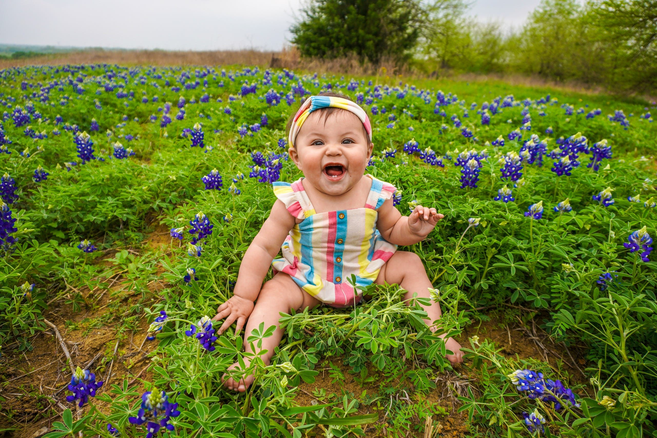 A baby is pictured sitting on grass and laughing. (Unsplash, Danny de los Reyes)